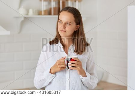 Indoor Shot Of Dreamy Woman With Dark Hair Wearing White Shirt Holding Cup With Coffee Or Tea, Looki