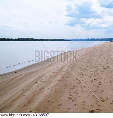 The Sandy Shore Of The Big Volga River Against The Background Of A Cloudy Sky