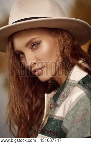 Autumn beauty woman. Portrait of a beautiful girl in a felt hat and a checkered flannel shirt on a background of autumn. Autumn colors.