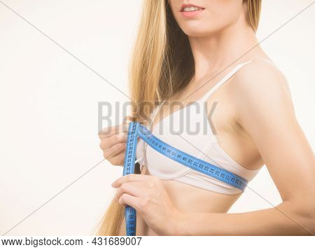 Girl Wearing White Bra Using Tape Measure To Check The Measurements Of Her Chest Breasts. Side View.