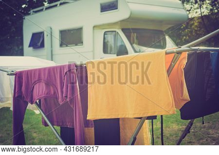 Clothes Clean Washing Laundry Hanging To Dry On Clothesline Outdoor, Caravan In The Background. Camp