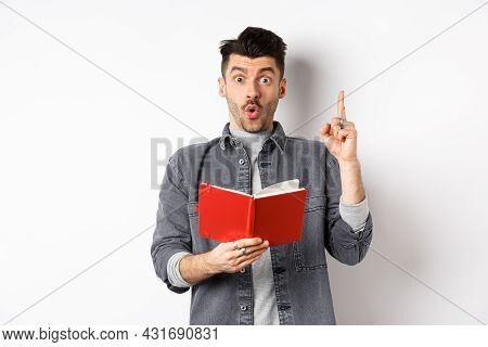 Excited Man Pitch An Idea While Reading Planner Or Diary, Holding Red Journal And Gasping Amazed, Ra