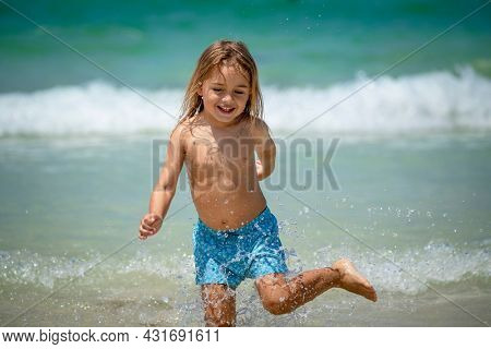 Portrait of a Cute Little Boy Running in the Water Making Splashes. Happy Child Enjoying Active Summer Holidays on the Beach Resort.