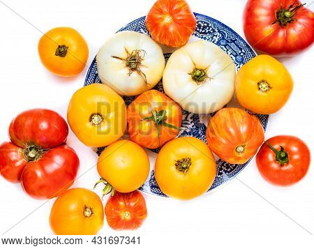 Heirloom Tomatoes Of Different Colors On A Blue Plate.