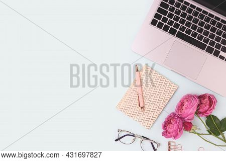 Feminine Workspace With Laptop, Flowers And Stationery On A Blue Background. Online Work Concept Wit