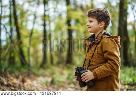 Portrait Of Boy Who Is Hiking In Nature With Binoculars In Autumn.
