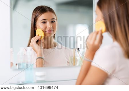 beauty, hygiene and people concept - teenage girl with cleansing sponge cleaning facial skin and ooking in mirror at bathroom