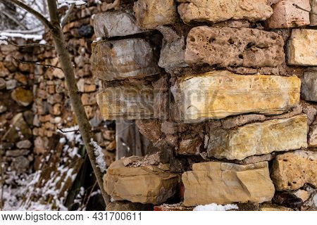 Close-up Photo Of An Ancient Stone Arch. Part Of An Old Brick Stone Arch In Winter. Ruins Of Weather