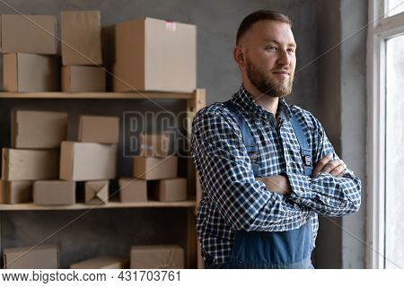 Young Caucasian Small Business Owner Stands Near A Rack With Boxes. Online Sales, E-commerce And Sma