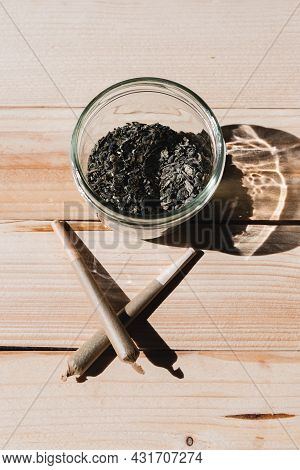 Overhead Shot Of A Jar With Crushed Cannabis And Two Crossed Joints On A Wooden Table. Concept Of Th