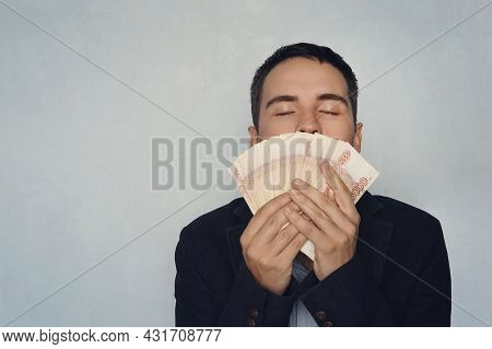 Man Sniffing Dollars. The Sweet Smell Of Money. Young Guy Sniffing 5000 Rubles Earned Money. Salary.