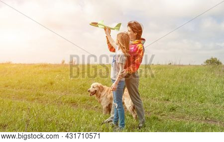 Mother and daughter with toy plane and golden retriever dog spending time at the field together. Girl, woman and pet doggy playing with airplane at the nature