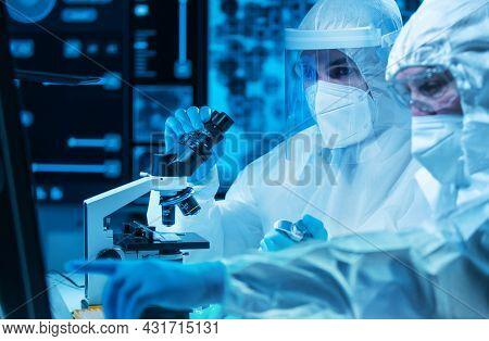 Scientists Work In A Modern Scientific Lab Using Laboratory Equipment, Microscope And Computer Techn
