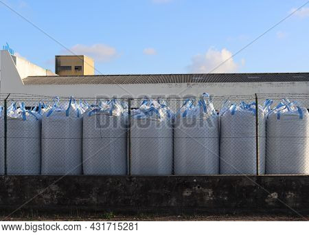 Large White Polypropylene Bags Stand Behind The Fence. Row Of Large Bags.