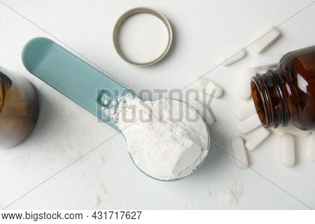 Measuring Scoop Of Amino Acids Powder And Pills On White Table, Flat Lay