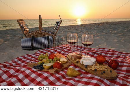 Blanket With Wine And Snacks For Picnic Near Basket On Sandy Beach