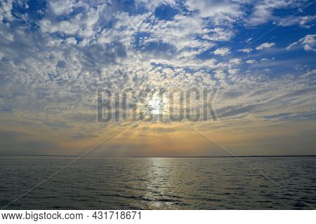 Sunset landscape with sunshine over water surface