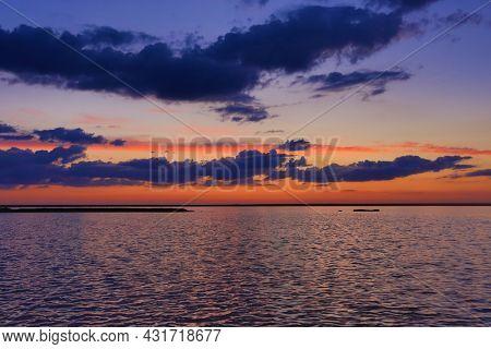 Nice evening sky over lake water surface. Sunset landscape on lake