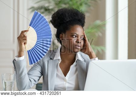 Tired Young African Businesswoman Hold Wave Fan Exhausted Of Heat Indoors Overheated At Workplace In