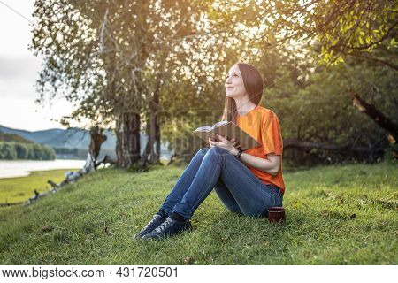 A Young Beautiful Woman In Bright Clothes Is Sitting On The Green Grass And Enjoying Reading A Book