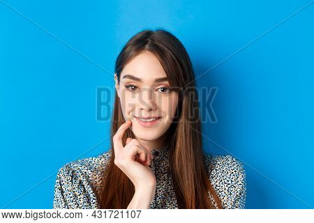 People Emotions Concept. Close-up Portrait Of Intrigued Pretty Lady Smiling And Looking Thoughtful,