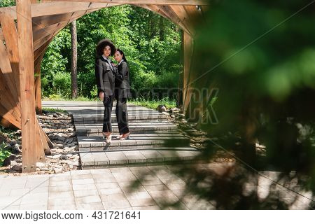 Multiethnic Lesbian Couple In Formal Wear Standing Under Arch