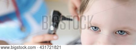 Doctor Examining Ear With Otoscope For Little Smiling Girl