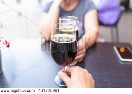 Woman And Man Drink Beer. Friends Met In A Pub. Two Glasses Of Dark Beer.two People Toasting With Gl