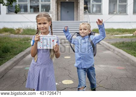 Elementary School Kids. Happy Girl Holds Picture With Back To School Message And Boy With Backpack R