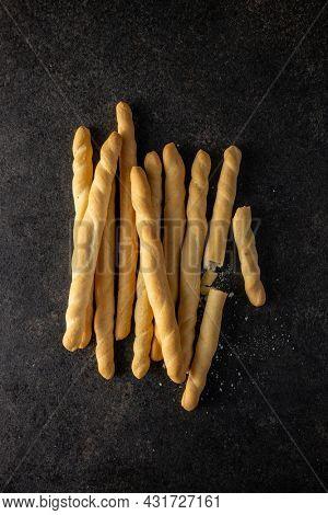Grissini sticks. Traditional italian bread sticks on black table. Top view.