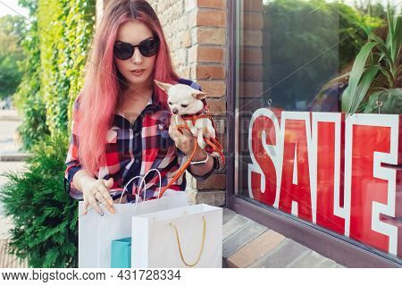 Close-up Of A Girl In Fashionable Clothes, Who Is Considering Purchases Near The Inscription Sale. W
