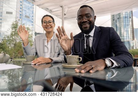 Asian and African white collar workers waving hands to their colleagues during online meeting in front of laptop in outdoor cafe
