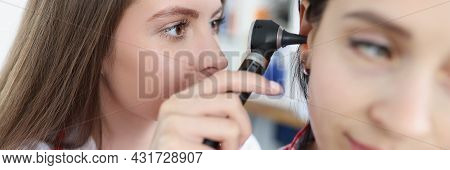 Doctor Therapist Examining Ear Of Woman Patient With Ostoscope In Clinic