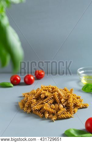 Raw Fusilli Pasta With Ingredients On A Gray Background. Whole Grain Pasta. Concept Of Traditional I