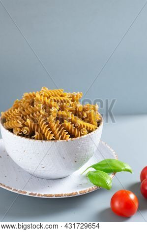 Raw Fusilli Pasta In A White Bowl With Cherry Tomatoes And Basil On A Gray Background. Whole Grain P