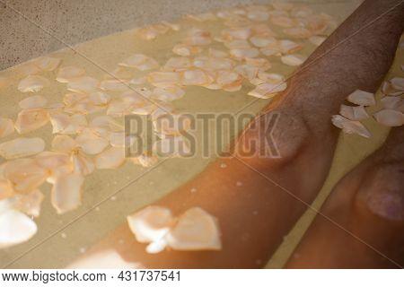 Male Hairy Legs, Water, Petals, Soap In Bath Tub.