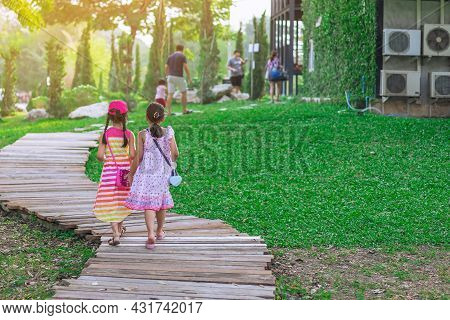 Back View Of Asian Little Girls In Dress Walking Side By Side On Pathway Through Green Garden.two Gi