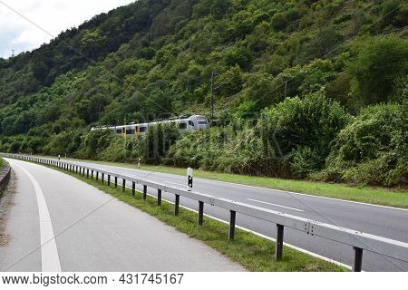 Boppard, Germany - August 24th 2021: Middle Rhine Road With A Train Passing By