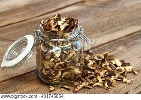 Dried Brown Bolete Mushrooms. Boletus Mushroom, Lat. Imleria Badia,  In A Jar On The Old Wooden Tabl