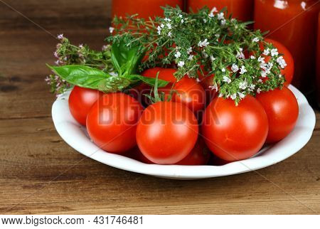 Homemade Preserved  Ketchup.  Fresh Tomatoes And Herbs Of Basil, Thyme And Savory In Front, Jars Of