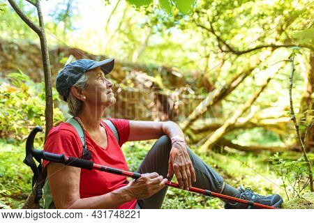 Older Woman In A Cap And Red T-shirt Takes A Break During A Hike In The Woodsolder Woman In A Cap An