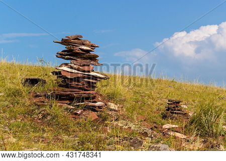 Cairn From Reddish Balanced Stones Of Devonian Sandstone On The Top Of Hill Against Blue Sky Backgro