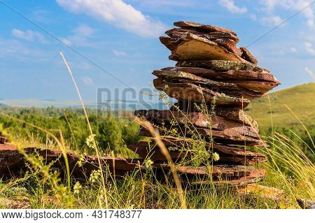Cairn From Reddish Stones Of Devonian Sandstone On Green Grass On The Top Of Hill Against Blue Sky B