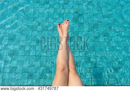 The Girl Sunbathes And Enjoys Relaxing By The Pool. Legs On The Background Of Water In The Pool.