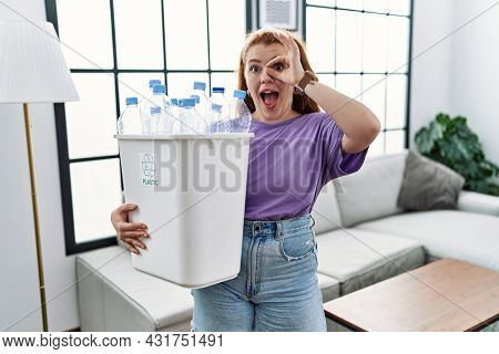 Young redhead woman holding recycling wastebasket with plastic bottles doing ok gesture with hand smiling, eye looking through fingers with happy face.