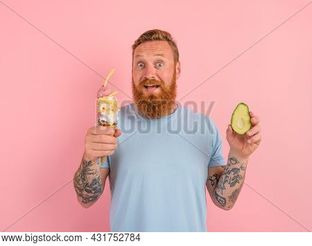 Amazed Man With Beard And Tattoos Is Undecided If To Eat An Icecream Or An Avocado