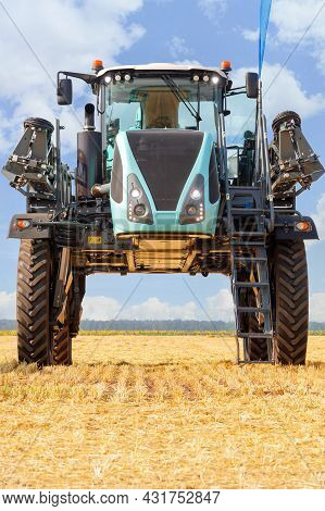 A Model Of A Self-propelled Sprayer With A High Wheelbase Against The Backdrop Of A Harvested Wheat