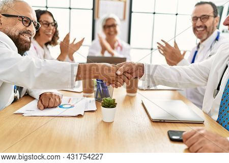 Group of middle age doctor smiling and clapping to partners handshake in a medical meeting at the clinic office.