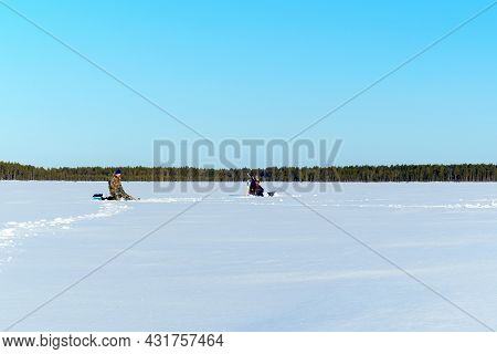 Ice Fishing. Fishermans Fishing On A Winter Lake Against A Background Of Forest And Blue Sky.