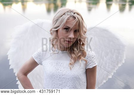 Portrait Of Blonde Woman In White Dress And White Angels Wings. Good People. Heaven, God. Paradise A